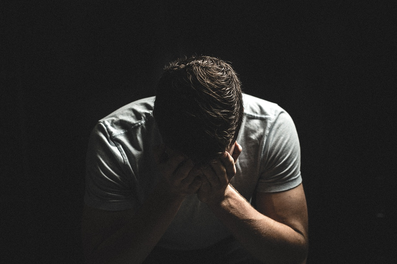 Male with head in hands in despair