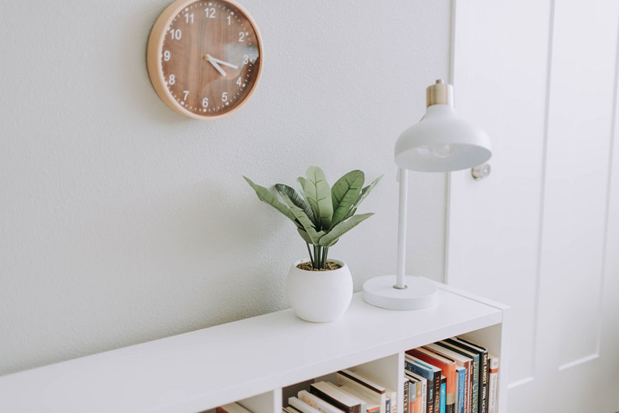 Bookshelf with plant on top, clock on the wall.