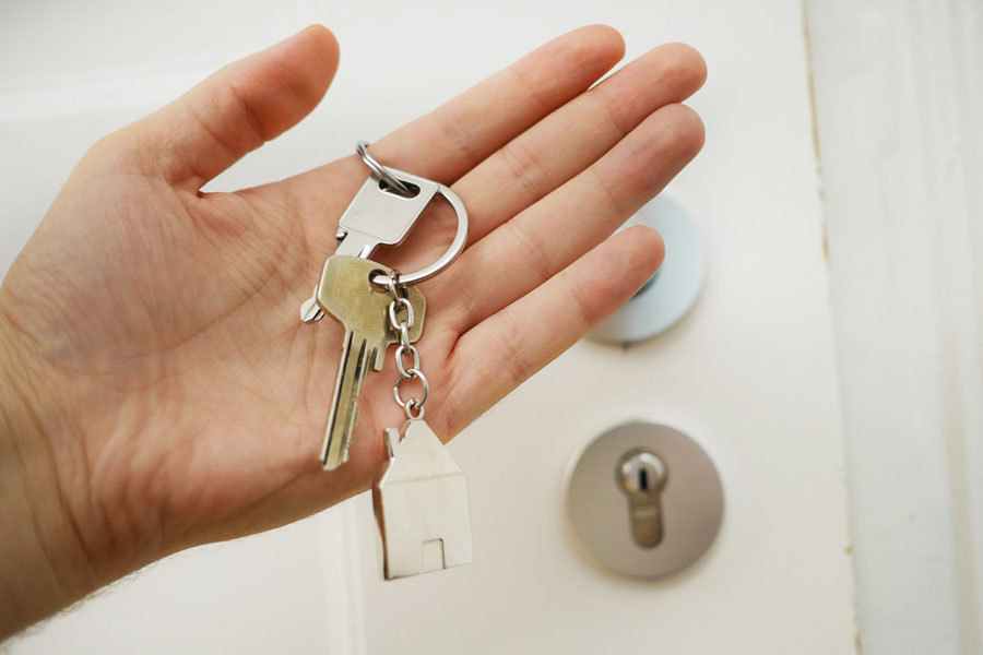 A hand with keys inside to the house